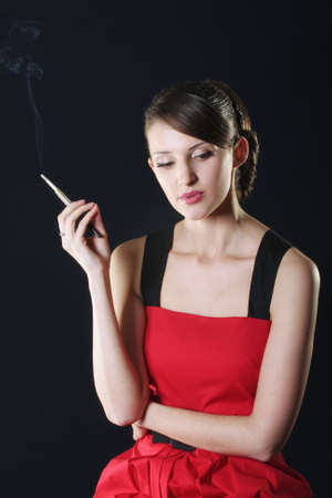 Thoughtful young attractive woman in red dress smoking photo