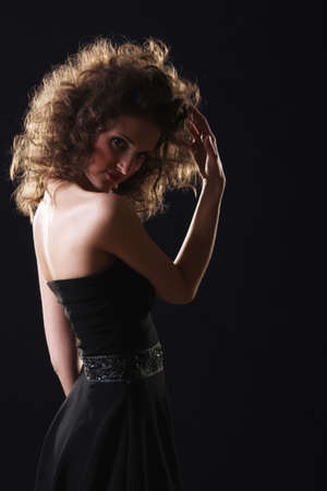 hairdress: Young woman with fluffy hairdress against dark background
