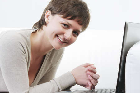 Pretty young smiling woman laying on white sofa with computer closeup photo photo