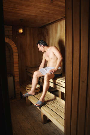 Man sitting in wooden sauna looking down at wash-tub Stock Photo - 6800893