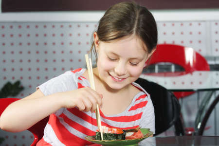 Little smiling girl eating sushi with wooden sticks