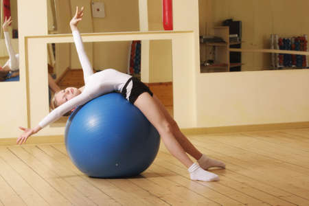 female gymnast: Little gymnast girl laying down on big blue ball in gym