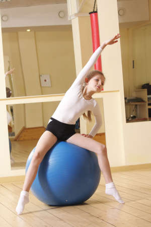 Little gymnast girl sitting on big blue ball in gym bending left photo