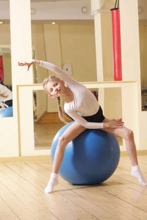 Little gymnast girl sitting on big blue ball in gym bending right side Stock Photo