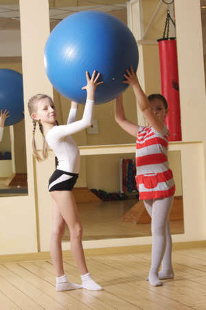 female gymnast: Two little girls in gym raising big blue ball over head