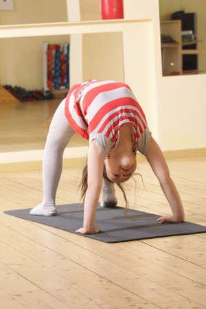 gym floor: Little gymnast girl in bridge stand on gray mat