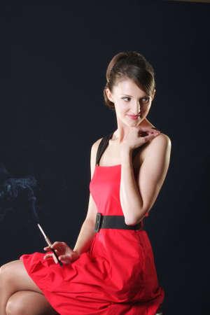 chica fumando: Joven con cigarrillos, sentado en la silla sobre fondo oscuro