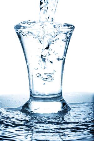 lekken: Verspilling van water lekken in overvolle glas foto tegen Wit