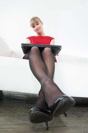 Woman in red sitting on sofa with closed laptop on knees photo