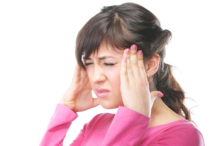 splitting headache: Young brunette woman in pink with racking headache photo with copyspace