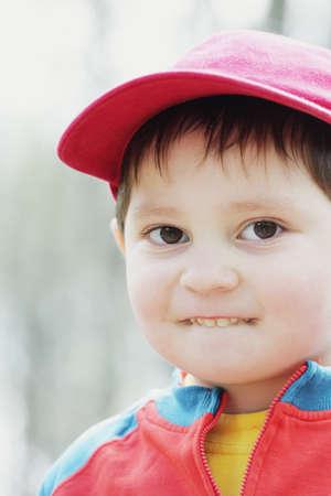 poco: Niño pequeño en la gorra roja morder la foto al aire libre de labio portarretrato