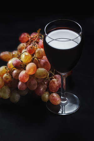 Grapes and red wine in glass in darkness closeup photo above view photo