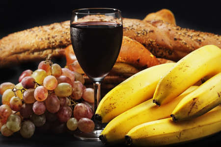Red wine with fruits and pastry against dark background photo