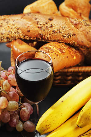 Red wine among fruits and pastry above view photo