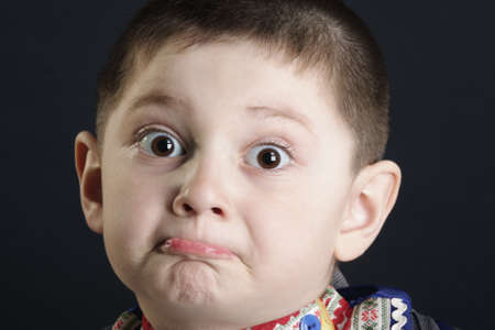 perplexity: Little cute boy in perplexity closeup photo against dark background Stock Photo