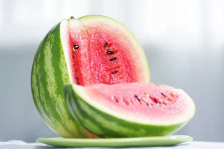 Cut striped watermelon laying on green plate selective focus