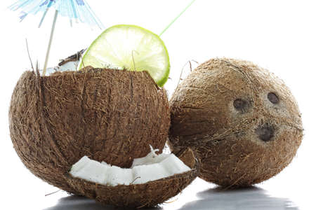 intact: Coconuts cracked and intact with reflections against white background  Stock Photo