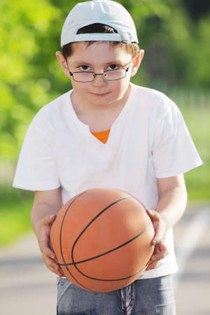 Little boy in eyeglasses standing with basketball outdoors
