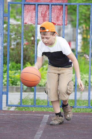 Boy in casual dribbling basketball on summer outdoor pitch