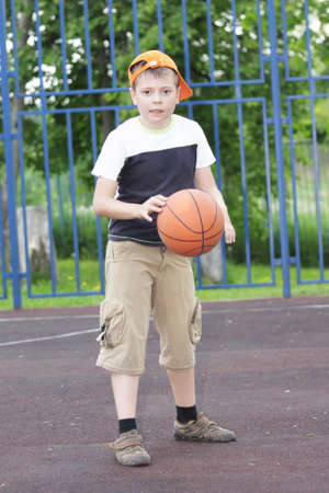 tapping: Boy in casual tapping basketball outdoors at summer sunlight pitch Stock Photo