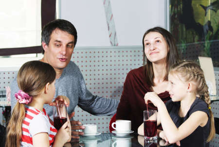 Dad talking to daughter while family sitting at cafe table photo