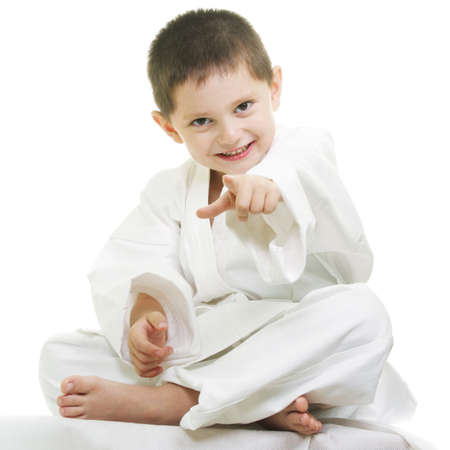Little karate kid sitting legs crossed pointing forward Stock Photo