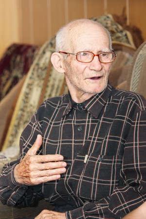 gesticulating: Senior man sitting on sofa talking and gesticulating