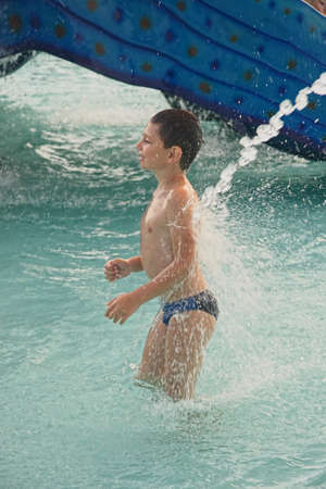 Little boy standing in swimming pool under water jet photo