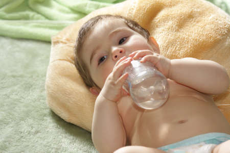 Little baby laying down on green rug with bottle Stock Photo