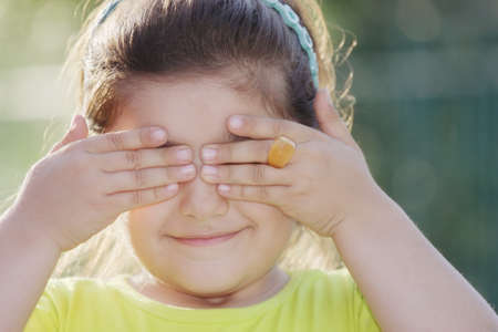 eyes closing: Little girl closing eyes closeup outdoor photo