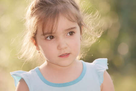 looking sideways: Little girl in summer sunlight looking sideways closeup photo