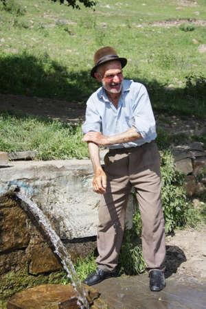 Smiling senior man in hat washing hands at spring Stock Photo - 7533766