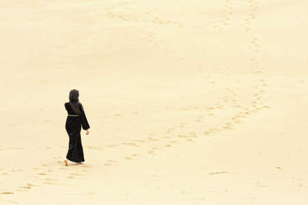Young woman in black dress walking by desert routes photo