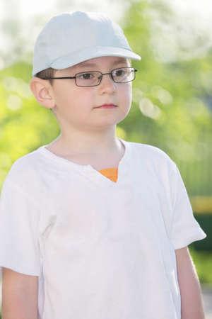 looking sideways: Cute kid in eyeglasses looking sideways closeup outdoors