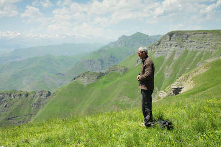 Senior man praying in summer mountains Stock Photo - 7625597