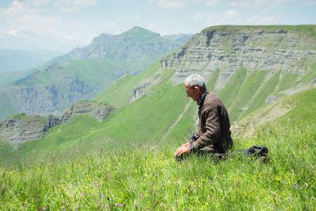 Senior man praying in summer mountains Stock Photo - 7625600