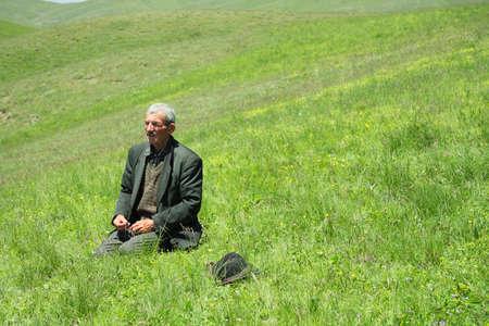 Senior man telling beads in mountain meadows closeup Stock Photo - 7625598
