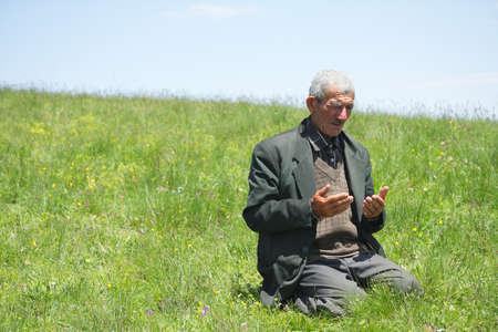 hombre orando: Senior hombre levantando las manos en oraci�n en colina cubierta de hierba
