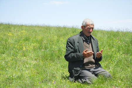 Senior man lifting hands in prayer  on grassy hill