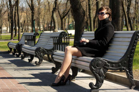overcoat: Young woman in black overcoat sitting on bench in springtime park