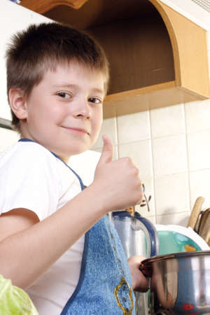 contented: Contented boy at kitchen showing thumb up gesture