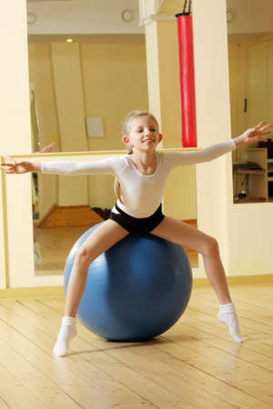 Little gymnast girl sitting on big blue ball in gym Stock Photo - 7671581