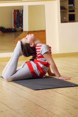 Little gymnast girl raising feet to head on gray mat