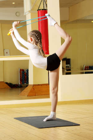Little gymnast working out in gym with skipping rope