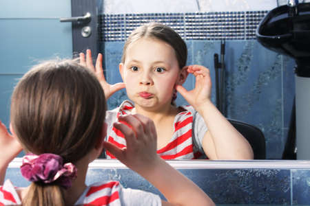 Little cute girl grimacing herself at mirror selective focus