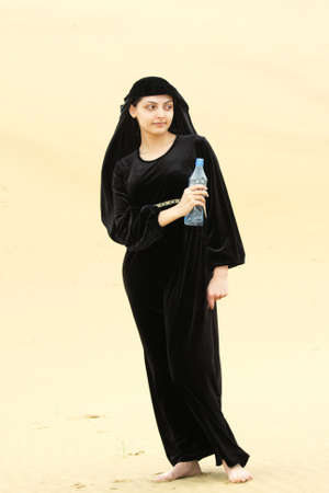 looking sideways: Young woman in desert withh bottle of water looking sideways Stock Photo