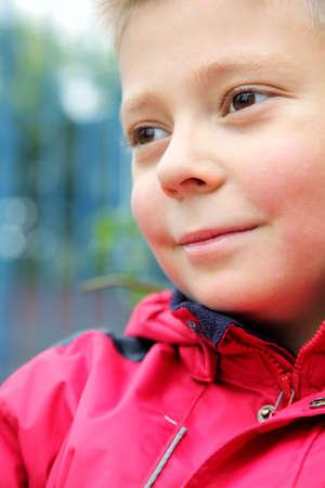 looking sideways: Cute boy in red jacket looking sideways closeup photo selective focus Stock Photo