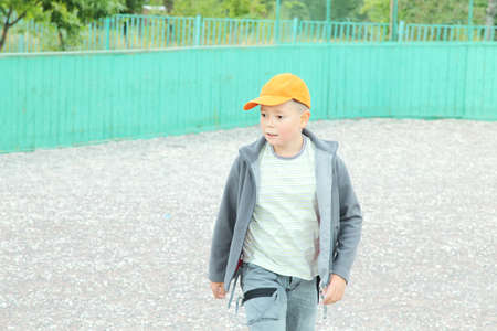 looking sideways: Boy in casual going by sports ground looking sideways Stock Photo
