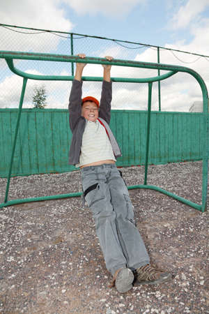 Smiling boy in casual clother hanging on goal outdoors Stock Photo - 7750422
