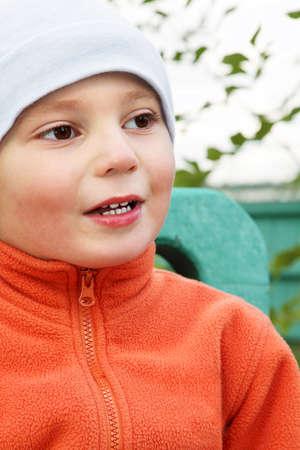 looking sideways: Little boy in orange jacket looking sideways closeup photo